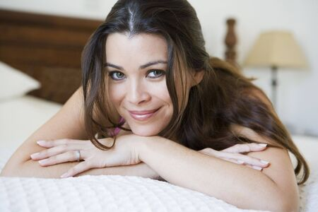 Woman relaxing on bed in bedroom smiling (selective focus) Stock Photo - 3186687