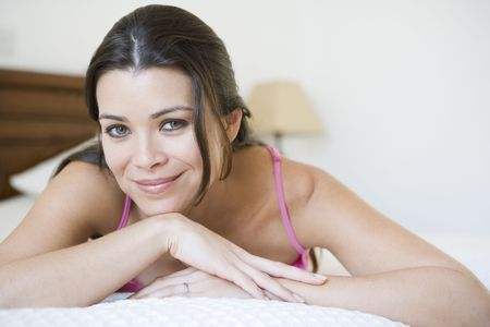 caucasoid race: Woman relaxing on bed in bedroom smiling (selective focus) Stock Photo