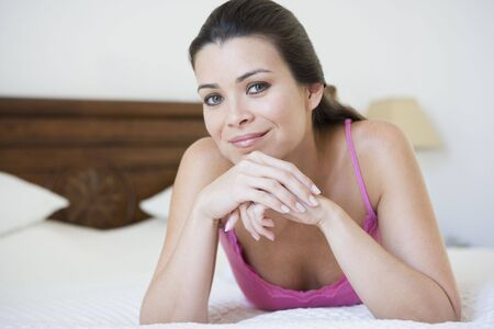 Woman relaxing on bed in bedroom smiling (selective focus) Stock Photo - 3186813