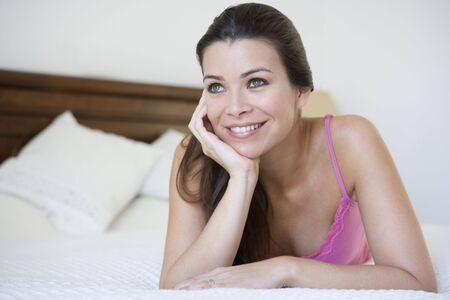 Woman relaxing on bed in bedroom smiling (selective focus) Stock Photo - 3186867