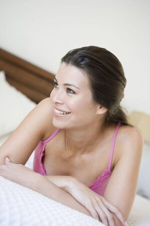 Woman relaxing on bed in bedroom smiling (selective focus) Stock Photo