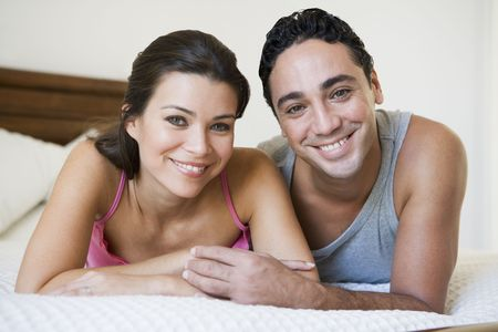 mid adult couple: Couple relaxing on bed in bedroom smiling (selective focus) Stock Photo