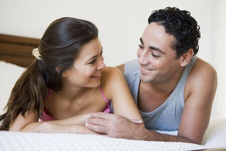 Couple relaxing on bed in bedroom smiling (selective focus) Stock Photo - 3186650