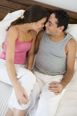 Couple relaxing on bed in bedroom snuggling and smiling (selective focus)