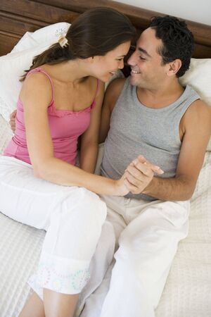 Couple relaxing on bed holding hands in bedroom smiling (selective focus) Stock Photo - 3186579