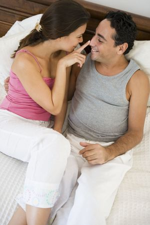Couple relaxing on bed in bedroom bonding and smiling (selective focus) photo