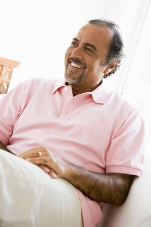 parlours: Man sitting in living room smiling (high key)