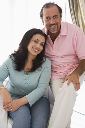 Couple in living room smiling (high key) Фото со стока