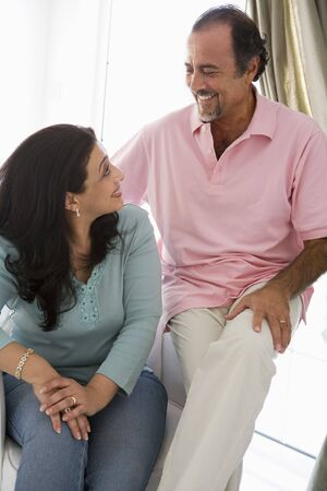 Couple sitting in living room smiling (high key) Stock Photo - 3186290
