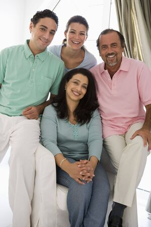Two couples in living room smiling (high key)