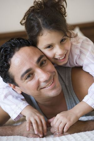 Father and daughter girl relaxing on bed in bedroom smiling (selective focus) Stock Photo - 3186586