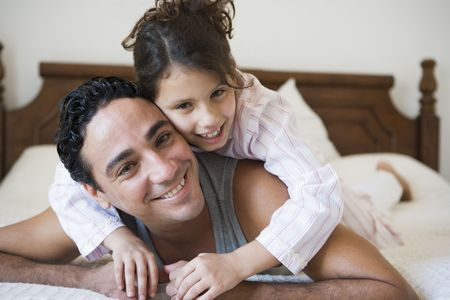 Man and young girl relaxing on bed in bedroom smiling (selective focus) photo