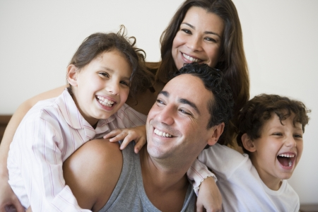 Family together on bed in bedroom smiling (selective focus) Stock Photo