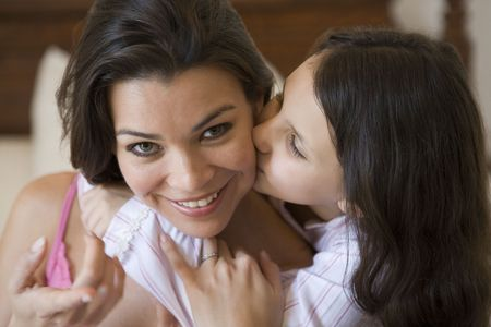 multi family house: Young girl kissing smiling woman on cheek in bedroom (selective focus)