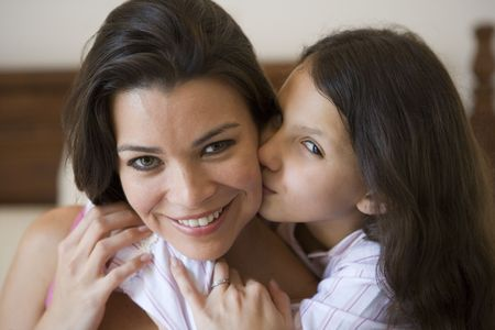 Young girl kissing smiling woman on cheek in bedroom (selective focus) photo