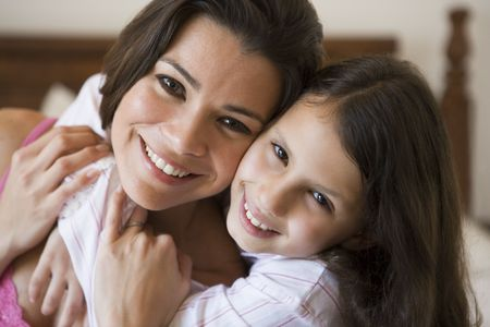 Woman and young girl in bedroom embracing and smiling (selective focus)
