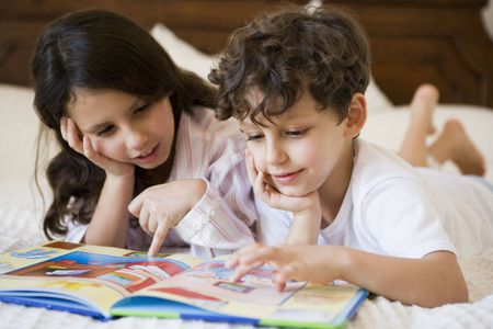 Two young children in bedroom reading book (selective focus) photo