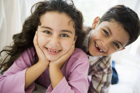 high key: Due giovani bambini che giocano nel salotto sorridente (alta chiave)