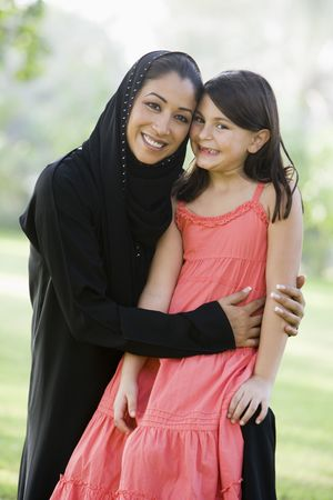 Woman and young girl outdoors in a park smiling (selective focus)