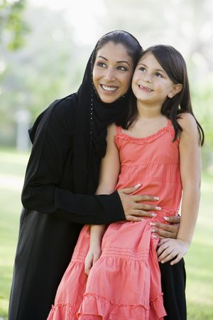 jilaabah: Woman and young girl outdoors in a park smiling (selective focus) Stock Photo