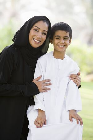 jilaabah: Woman and young boy outdoors in a park smiling (selective focus)