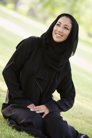 jilaabah: Woman sitting outdoors in park smiling (selective focus) Stock Photo