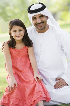 dishdashas: Man and young girl outdoors in a park smiling (selective focus)