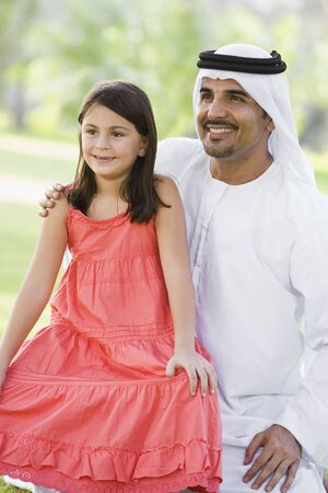 Man and young girl outdoors in a park smiling (selective focus)