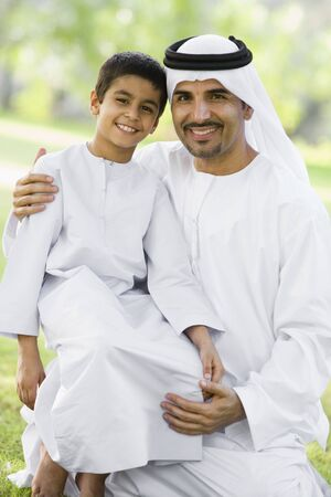 thobe: Man and young boy outdoors in a park smiling (selective focus)