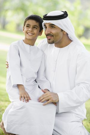 khameez: Man and young boy outdoors in a park smiling (selective focus)