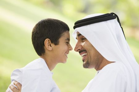 dishdasha: Man and young boy outdoors in park smiling (selective focus)