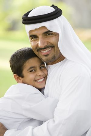 Man and young boy outdoors in park embracing and smiling (selective focus)