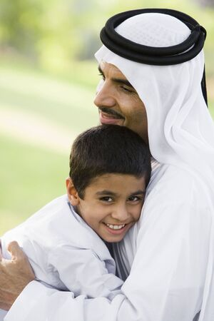 dishdashas: Man and young boy outdoors in park embracing and smiling (selective focus)