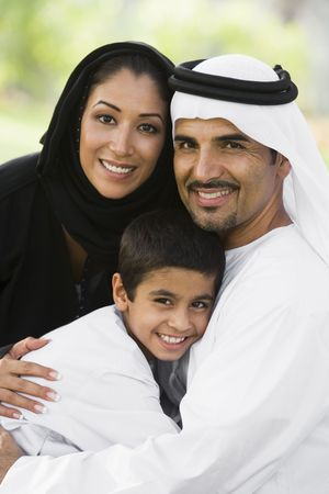 kanduras: Family outdoors in park embracing and smiling (selective focus)