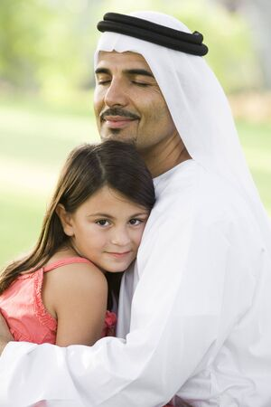 agal: Man and young girl outdoors in park embracing and smiling (selective focus)