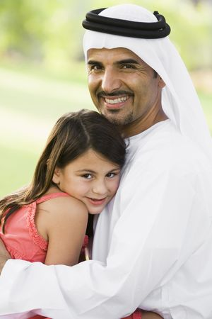 Man and young girl outdoors in park embracing and smiling (selective focus)