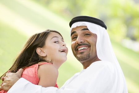 Man and young girl outdoors in park playing and smiling (selective focus) photo