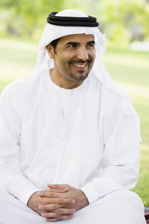 thawbs: Hombre sentado al aire libre en el parque sonriendo (atenci�n selectiva)