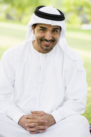 thobes: Man sitting outdoors in park smiling (selective focus) Stock Photo