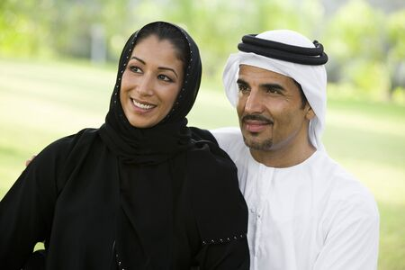thobes: Couple outdoors in park smiling (selective focus) Stock Photo