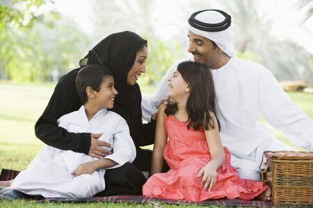 femmes muslim: Famille en plein air dans un parc ayant un pique-nique et souriant (s�lective focus)