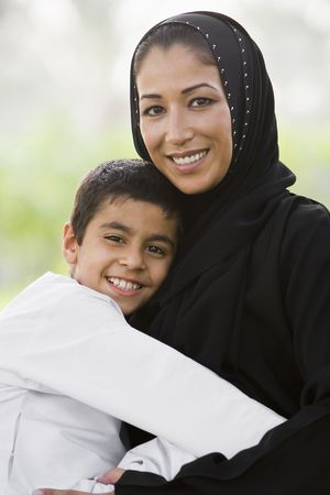 jilaabah: Woman and young boy outdoors in park embracing and smiling (selective focus)