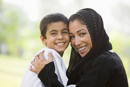 jilaabah: Mother and son outdoors in park embracing and smiling (selective focus)