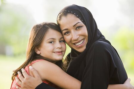 jilaabah: Mother and daughter outdoors in park embracing and smiling (selective focus) Stock Photo