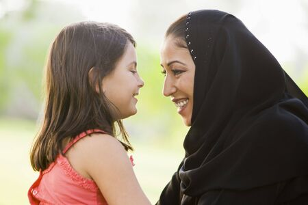Mother and daughter outdoors in park embracing and smiling (selective focus) photo