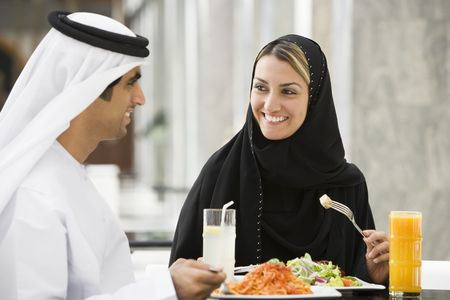 Couple at restaurant eating and smiling (selective focus) photo