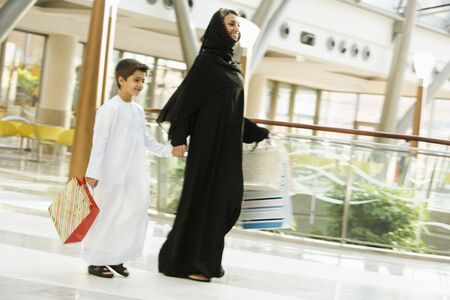 windowpanes: Woman and young boy walking in mall smiling (selective focus)