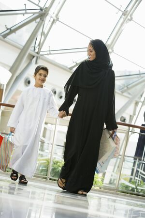 jilaabah: Woman and young boy walking in mall smiling (selective focus)