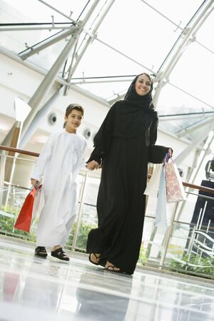 Woman and young boy walking in mall smiling (selective focus) photo