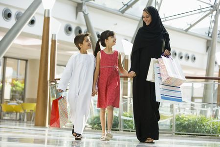 Woman and two young children walking in mall smiling (selective focus) photo